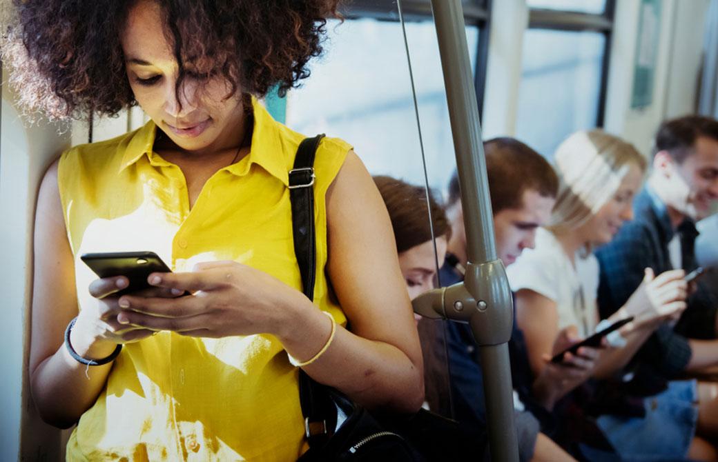 電車内でスマホを見る女性